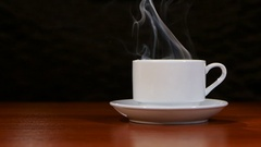 Cup of coffee costs on a wooden table and spreads a pleasant smell Stock Footage
