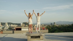 CLOSE UP: Happy young couple standing on rooftop and raising hands in the sky Stock Footage