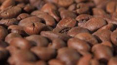 Grains of coffee on a table torque and release smoke. Close-up Stock Footage