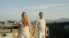 CLOSE UP: Happy man and smiling woman standing on rooftop raising hands Stock Footage
