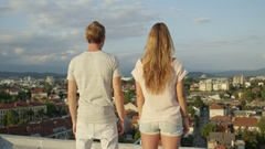 CLOSE UP: Happy boyfriend hugging his beautiful girl on roof of a skyscraper Stock Footage