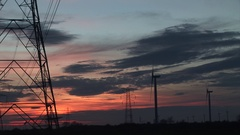 Evening light with pylons and wind turbines in England Stock Footage