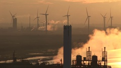 Power station and steam with wind turbines in the background Stock Footage