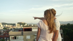 CLOSE UP: Boyfriend showing girlfriend city pointing on the rooftop above town Stock Footage