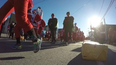Santa suit runners go by the camera Stock Footage