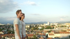 CLOSE UP: Boyfriend pointing with fingers showing city to girlfriend at rooftop Stock Footage