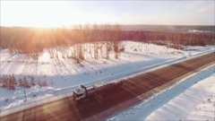 Slowmotion. Many trucks drives on snow highway in sunsets. Snow flakers falling Stock Footage