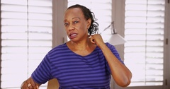 An African American woman has joint and muscle pain while talking to the camera Stock Footage