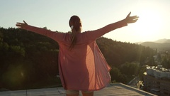 CLOSE UP: Cheerful young woman raising hands and spinning on top of skyscraper Stock Footage