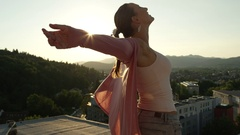 CLOSE UP: Happy young woman spinning with hands raised on the top of skyscraper Stock Footage