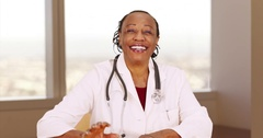 An older black doctor happily giving medical advice in a video chat Stock Footage
