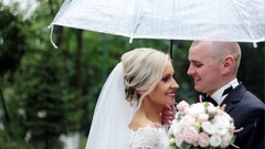 The bride and groom in the rain are covered with a transparent umbrella Stock Footage