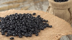 Close-up of black beans rotating on burlap. Rustic wooden background. Seamless Stock Footage