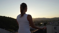 CLOSE UP: Yoga girl sitting on the edge on rooftop, meditating in lotus pose Stock Footage
