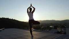 CLOSE UP: Woman relaxing doing tree pose on the top of skyscraper at sunset Stock Footage