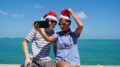 Happy couple wear Santa's Hat making selfie with smartphone on the beach Stock Footage