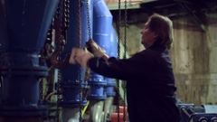 Woman pulled the chain and move hoist Stock Footage