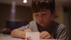 A little boy setting up a homemade name tag on the counter Stock Footage