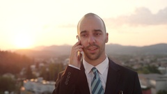 CLOSE UP: Businessman talking on mobilephone on rooftop at amazing sunrise Stock Footage