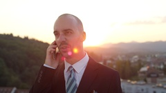 CLOSE UP: Smiling businessman speaking on smartphone on rooftop at golden sunset Stock Footage