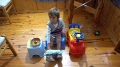 Child on potty chair with his toys food and drink Stock Footage