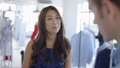 4K Woman shopping in clothing store makes contactless payment with smartphone Stock Footage