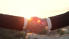 CLOSE UP: Business hand shake at sunset with beautiful cityscape in background Arkistovideo
