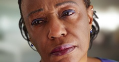 A close-up of a elderly black woman looking off in the distance sadly Stock Footage