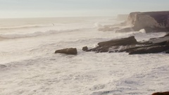 Waves Crashing Against Cliff And Rocks At Sunset Stock Footage