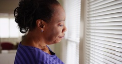 An older black woman mournfully looks out her window Stock Footage