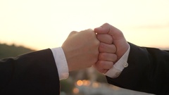 CLOSE UP: Business fist-bump at sunset with beautiful cityscape in background Stock Footage