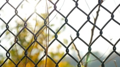 Chainlink fence in sharp focus with soft background and sunlight. Stock Footage