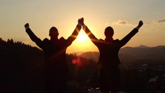 CLOSE UP: Two businessmen on the top of skyscraper with hands raised at sunset Stock Footage