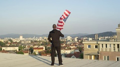 CLOSE UP: Businessman looking proudly down on his hometown holding American flag Stock Footage