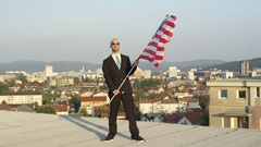 CLOSE UP: Man in uniform holding American flag in his hands on tall skyscraper Stock Footage