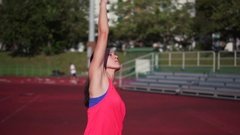 Asian woman stretching and exercising on a track in evening sun Stock Footage