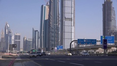 Ground level Dubai car traffic on highway with modern business skyscrapers view Stock Footage