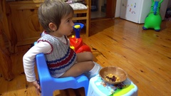 Child on potty chair watching TV Stock Footage