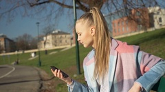 Pretty girl looks annoyed while waiting for someone in the park, steadycam shot Stock Footage