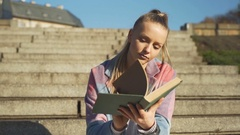 Pretty girl sitting on the stairs and reading book, steadycam shot Stock Footage