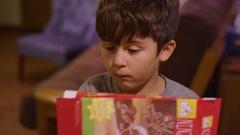 A little boy cutting open a cardboard box with scissors Stock Footage