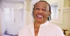 An elderly black woman happily poses for a portrait in his upscale bathroom Stock Footage
