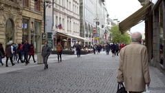 People walk down cobble stone street, old city Prague, Czech Republic Stock Footage
