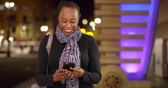An older black woman uses her phone at night Stock Footage