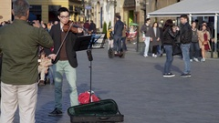 Young asian violinist performs busks at Prague old town square, Czech R. Stock Footage