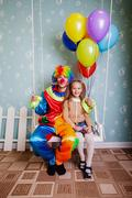 Little girl with the clown shake on a swing. Stock Photos