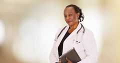 An older black doctor posing for a portrait in her office Stock Footage