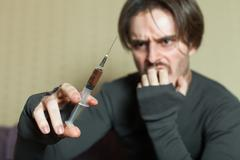 Abuse addict man with syringe in hand. Stock Photos
