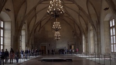 Tourists walk inside royal family palace dining hall, chandeliers, Prague Stock Footage