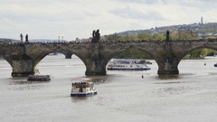 Boat ships in Vltava river, people walk across Charles bridge, Prague, Czech R. Stock Footage